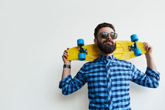 Skateboarder som rymmer en skateboard bak hans huvud royaltyfria foton