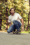 Skateboarder squatting on a skateboard and ride through the fore Stock Image