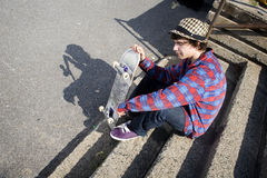 Skateboarder on stairs holding his board Stock Images
