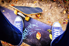 Skateboarder standing on a bench in city park royalty free stock image