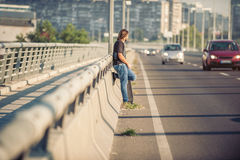 Skateboarder standing on the bridge leaning on a fence and watch. Skateboarder standing on the city road bridge leaning on a fence and watching traffic. Urban stock images