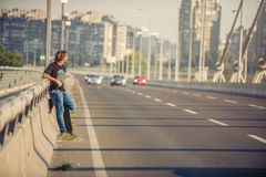 Skateboarder standing on the bridge leaning on a fence and watch. Skateboarder standing on the city road bridge leaning on a fence and watching traffic. Urban royalty free stock photo