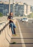 Skateboarder standing on the bridge leaning on a fence and watch. Skateboarder standing on the city road bridge leaning on a fence and watching traffic. Urban stock photo