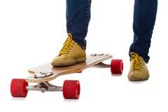 Skateboarder standing on a longboard skateboard Stock Photography