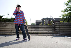 Skateboarder standing in parking Stock Photos