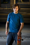 Skateboarder standing in underground parking lot Royalty Free Stock Images