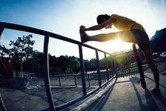 Skateboarder stretching legs Royalty Free Stock Photography