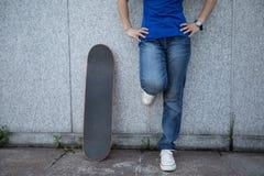 skateboarder tribune die op marmeren muur bij stad leunen royalty-vrije stock afbeelding