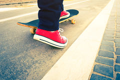 Skateboarder trick in beach road Stock Photography