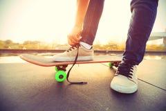 Skateboarder tying shoelace on city Royalty Free Stock Image