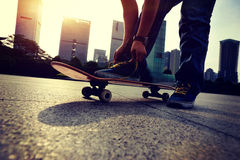 Skateboarder tying shoelace at modern city Stock Photography