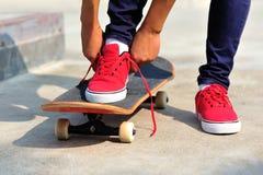 Skateboarder tying shoelace at skate park Royalty Free Stock Photo