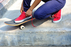 Skateboarder tying shoelace at skate park Royalty Free Stock Photography