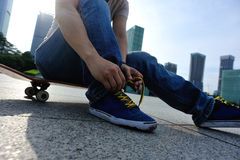 Skateboarder tying shoelace at skate park Royalty Free Stock Images