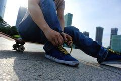 Skateboarder tying shoelace at skate park Royalty Free Stock Images