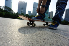 Skateboarder tying shoelace at skate park Royalty Free Stock Image