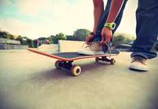 Skateboarder tying shoelace at skate park Stock Photography