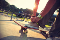 Skateboarder tying shoelace at skate park Stock Photos
