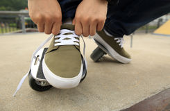 Skateboarder tying shoelace at skatepark ramp Royalty Free Stock Photography
