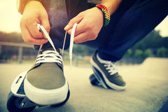 Skateboarder tying shoelace at skatepark ramp Royalty Free Stock Image