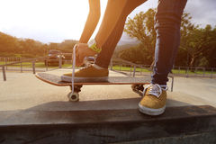 Skateboarder tying shoelaces at skate park Royalty Free Stock Images