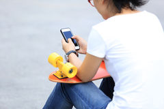 Skateboarder use cellphone sit on city stairs Royalty Free Stock Photography
