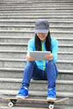 Skateboarder use digital tablet sit on stairs Royalty Free Stock Image