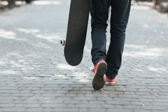 Skateboarder walk at street. City life concept. Of urban culture. Lifestyle person on footwear with skate. Red sneakers or gumshoes Royalty Free Stock Images