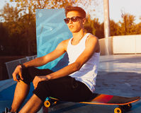 A skateboarder wearing white shirt, shorts is sitting in a skate-park on a sunset. Street foto with flare light of a young man on Stock Photos