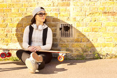 Skateboarder. Young woman sitting relaxing with her skateboard Stock Photography