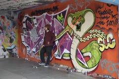 Skateboarderbenägenhet mot en vägg royaltyfri bild