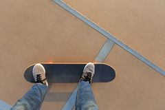 Skateboarderbenen die bij skatepark met een skateboard rijden Stock Foto's