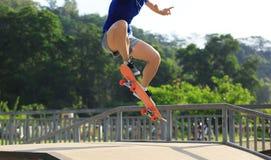 Skateboarderbenen die bij skatepark met een skateboard rijden Royalty-vrije Stock Afbeelding