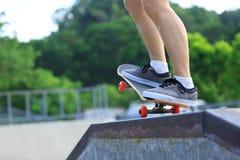 Skateboarderbenen die bij skatepark met een skateboard rijden Royalty-vrije Stock Foto's
