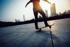 Skateboarderbenen die bij zonsopgangstad met een skateboard rijden Stock Foto's