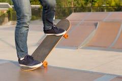 Skateboarderbenen die op skatepark met een skateboard rijden Stock Foto