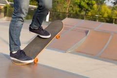 Skateboarderbenen die op skatepark met een skateboard rijden Royalty-vrije Stock Afbeeldingen