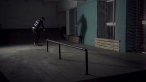 Skateboarderdia onderaan de leuningen op een skateboard stock videobeelden