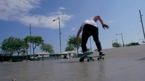 Skateboarderen gör ett trick utomhus arkivfilmer