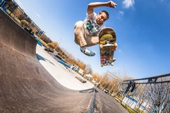Skateboarderen gör trick utan ben, höjdhoppet i mini- ramp i skatepark arkivbilder