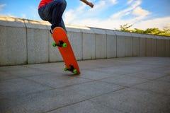 Skateboarderen lägger benen på ryggen hoppa en ollie Arkivfoton