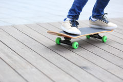 Skateboarderen lägger benen på ryggen ridning på skateboarden på stad Royaltyfri Foto