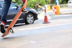 Skateboarderen lägger benen på ryggen ridning på skateboarden på stad Royaltyfria Bilder