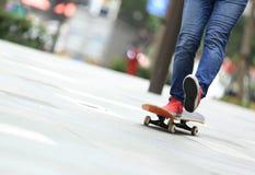 Skateboarderen lägger benen på ryggen ridning på skateboarden på stad Royaltyfria Foton