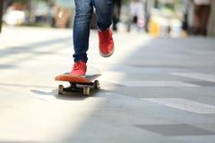 Skateboarderen lägger benen på ryggen ridning på skateboarden på stad Arkivfoton