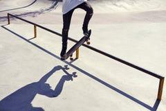 Skateboarderen som gör ett trick i en skridsko, parkerar, övar fristil e arkivfoto