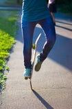 Skateboarderflicka` s lägger benen på ryggen i gymnastikskor som utomhus gör ett trick på skateboarden Royaltyfri Bild
