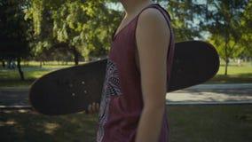 Skateboardergangen in een park met een skateboard in handen stock footage