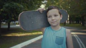 Skateboardergangen in een park met een skateboard in handen stock videobeelden