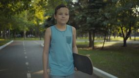 Skateboardergangen in een park met een skateboard in handen stock video